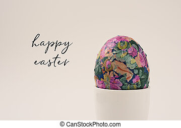 homemade decorated easter egg in an egg-cup