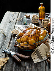 Homemade delicious baked chicken or turkey with whole baby potatoes in glass pan with copper stand on rustic wooden table