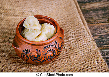 Homemade dumplings decorated in a clay pot on a linen napkin on a wooden background.