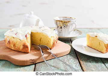 Homemade English cake with apples and whipped cream served with tea on blue wooden background