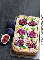 Homemade fig pie with brie cheese and almonds on black stone background