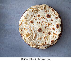Homemade flour tortilla on water lies in a pile