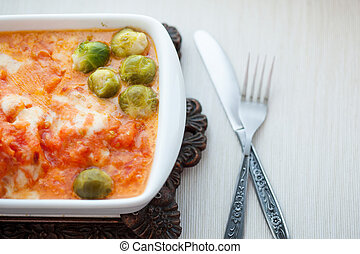 homemade food, stew red fish in sauce with Brussels sprouts