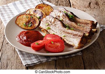 Homemade Fried Pork Ribs with Potatoes on a Plate. horizontal