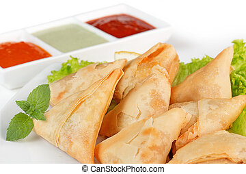 homemade fried samosas and sauces on white background