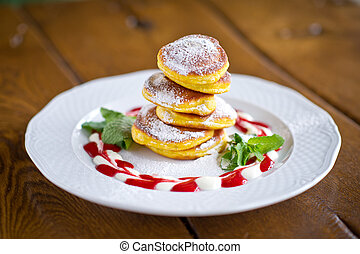 Homemade fritters of cottage cheese with nicely decorated strawberries sauce, sugar powder