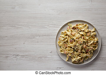 Homemade Garlic Shrimp Bacon Alfredo on a plate on a white wooden background, top view. Flat lay, overhead, from above. Copy space.