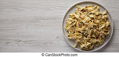 Homemade Garlic Shrimp Bacon Alfredo on a plate on a white wooden background, top view. Flat lay, overhead, from above. Space for text.