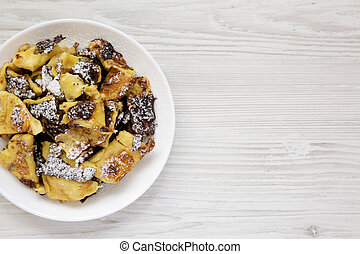 Homemade german Kaiserschmarrn pancake on a white wooden background, top view. Flat lay, overhead, from above. Space for text.