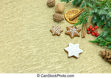 gingerbread cookies with fir tree branches, spice and red berries on gold wrapping paper