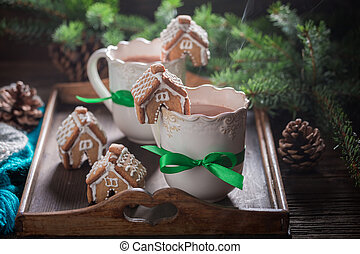 Homemade gingerbread cottages with sweet drink in Christmas evening