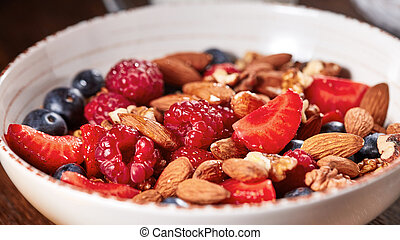 Homemade granola in a bowl, strawberries, almonds, blueberries, raspberry, honey - ingredients for natural breakfast.