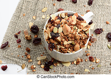 Homemade granola in a glass jar on white background