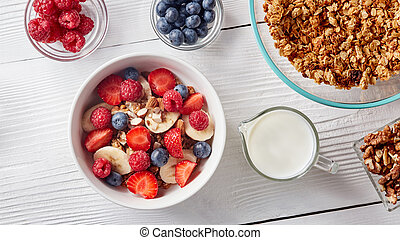Homemade granola in a plate, sliced banana and strawberries, milk, almonds, blueberries - ingredients for natural breakfast on wthite table.