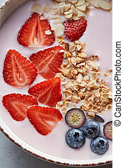 Homemade granola in a plate, sliced strawberries, yogurt, almonds, blueberries - ingredients for natural breakfast on a gray table.