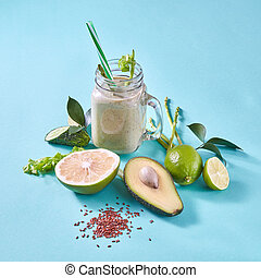 Homemade green smoothies with slices lemon, lime, avocado, selery, cucumber with flax seeds on a blue paper background.