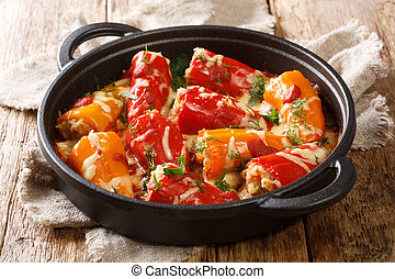Homemade hearty baked stuffed peppers with tomato sauce and cheese close-up in a frying pan. horizontal