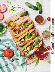 Homemade hot-dogs with fresh vegetables and spices over white background