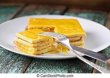 Homemade imperfect lemon cake on white plate