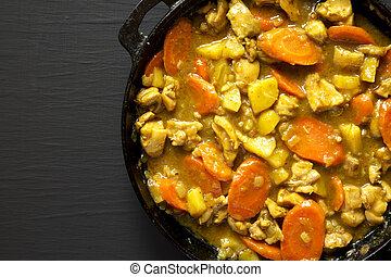 Homemade Japanese Chicken Curry in a cast-iron pan on a black background, top view. Flat lay, overhead, from above. Space for text.