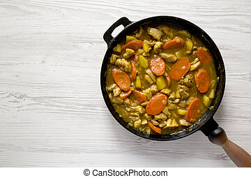 Homemade Japanese Chicken Curry in a cast-iron pan on a white wooden surface, top view. Flat lay, overhead, from above. Space for text.