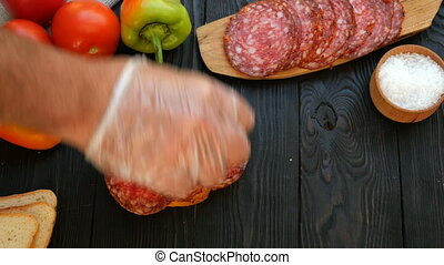 Homemade kitchen. Human hands preparing sandwich of chopped salami and tomato. Concept of making fast food.