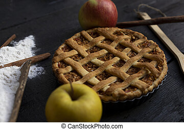 Homemade lattice Apple pie with cinnamon on an old textured wooden background