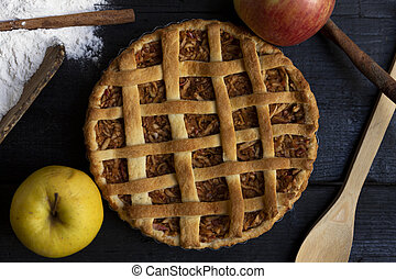 Homemade lattice Apple pie with cinnamon on an old textured wooden background. Top view