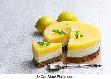 Homemade Layered Lemon Cheesecake on white wooden table
