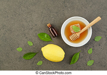 Homemade lemon essential oil, salt bath and fresh honey in the plate with honeycomb, dipper and mints on rustic background from top view. Flat lay good for background and space.