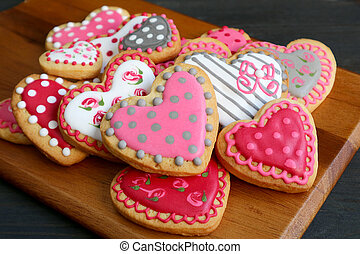 Homemade lovely patterned heart shaped royal icing cookies on  wooden breadboard