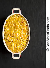 Homemade Macaroni and Cheese Pasta on a black surface, top view. Flat lay, overhead, from above. Copy space.