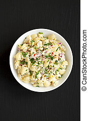 Homemade Macaroni Salad in a white bowl on a black background, top view. Flat lay, overhead, from above.