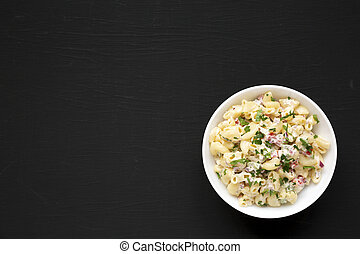 Homemade Macaroni Salad in a white bowl on a black background, top view. Flat lay, overhead, from above. Copy space.