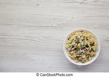 Homemade Macaroni Salad in a white bowl on a white wooden background, top view. Flat lay, overhead, from above. Space for text.