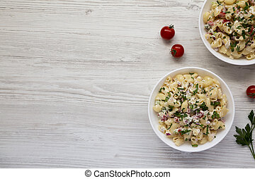 Homemade Macaroni Salad in white bowls on a white wooden background, top view. Flat lay, overhead, from above. Copy space.
