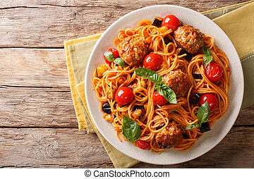 Homemade meat balls with spaghetti, aubergines and tomatoes close-up. horizontal top view