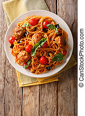 Homemade meat balls with spaghetti, aubergines and tomatoes close-up. Vertical top view