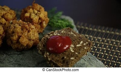 Homemade meat cutlets in batter with parsley, ketchup and bread on stone