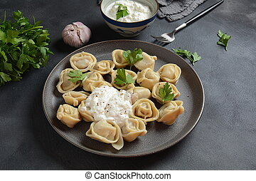 Homemade Meat Dumplings  served with sour cream and  fresh parsley on plate. Traditional Russian food- pelmeni, ravioli