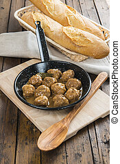 Homemade meatballs with onion sauce in a saucepan on the...