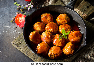 Homemade Meatballs with spices and tomato sauce in a frying pan on dark stone table. Free space for your text.