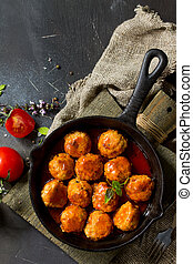 Homemade Meatballs with spices and tomato sauce in a frying pan on dark stone table. Free space for your text. Flat lay, top view background.