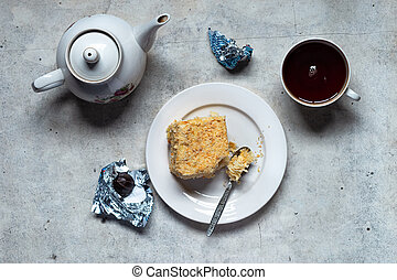 Homemade mille-feuille, puff pastry custard cream pie on white plate, chocolates, tea kettle and cup on gray background
