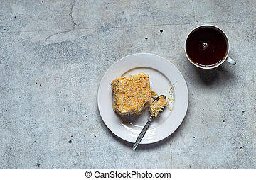 Homemade mille-feuille, puff pastry custard cream pie on white plate, cup of tea on gray background