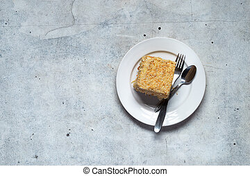 Homemade mille-feuille, puff pastry custard cream pie on white plate on gray background