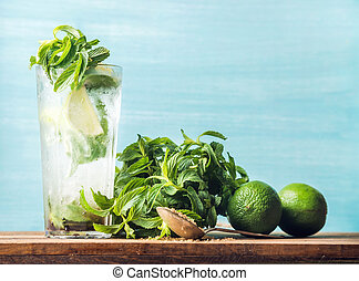 Homemade Mojito cocktail in tall glass with bunch of mint, brown sugar and limes