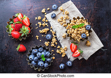 Homemade muesli granola in bowl with berries on rusty table