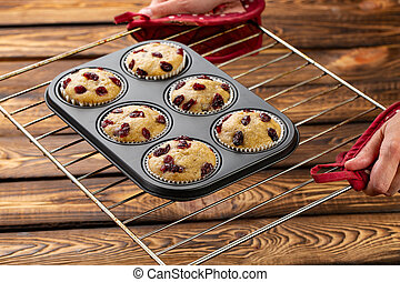 Homemade muffins with cherry in a baking form on the broun...