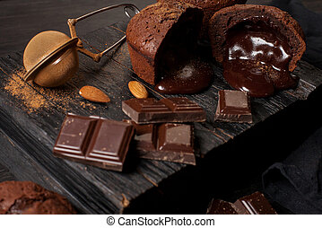 homemade muffins with chocolate, chocolate bars and almonds grains on a black wooden background.